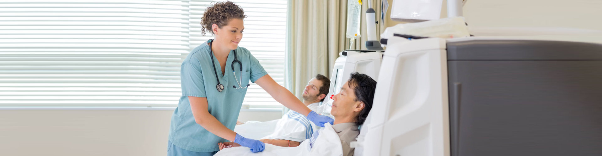 Female nurse assisting patient undergoing renal dialysis in hospital room