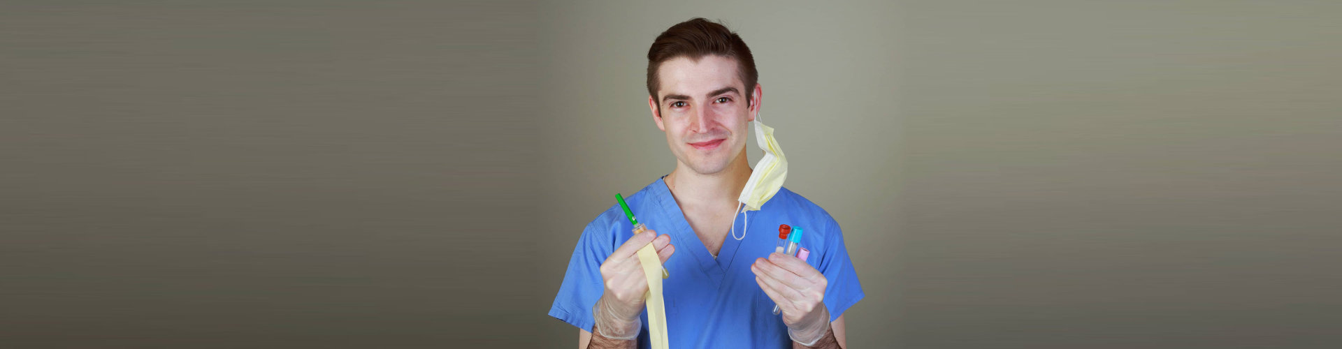 Young male phlebotomist with equipment for drawing blood